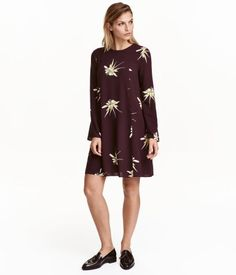 Plum/floral. Short, gently flared dress in woven viscose fabric with a relaxed fit. Opening at back of neck with covered buttons. Long, flared sleeves.