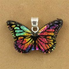 This pretty pendant is crafted from dichroic glass.  The smooth black background hosts richly detailed, shimmering butterfly wings.  The butterfly shapes continue throughout the pendant, while the vibrant and iridescent color shifts with movement.  A ster