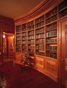 Curved bookshelves and wainscot paneling throughout the room. Dentil crown mouldings and architraves with Base mouldings and plinth blocks. Clear lacquer on cherry wood.