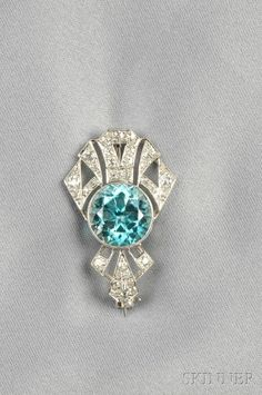 Art Deco Platinum, Blue Zircon, and Diamond Brooch, bezel-set with a circular-cut blue zircon measuring approx. 11.80 x 8.50 mm, further set with old European- and single-cut diamonds, millegrain accents, lg. 1 3/8 in.