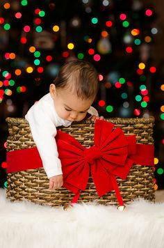 Baby in Christmas basket with Christmas lights