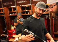 Cardinals Daniel Descalso signs a bat for pitcher Jason Motte as they clean out their lockers in the club house Tuesday, Oct. 23, 2012.
