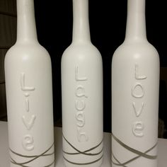 Words written with Elmer's glue on bottles, rubber bands on the bottom & them spray painted white. Remove rubber bands and then...Ta-Da!!   :o)
