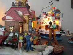 My Christmas Addiction by Andrew Stack on Capture Minnesota // This is a small corner of my annual Christmas Village display. The car ferry, lighthouse and seagulls are a tribute to the Puget Sound in Washington State.  I call it my Christmas addiction because it started with one Christmas Village house about 15 years ago.