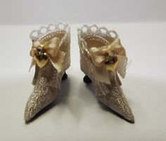 A pair of victorian style wedding ankle boots made from cream silk brocade and pure cream silk. The backs are embellished with cream lace and cream piping. The fronts of the boots have tiny cream silk bows with a golden heart and rhinestone decoration. The soles and heels are hand crafted in black.  The boots come with box and carrier bag.  Shoes are for display only. This is a collectors miniature and is not suitable for children under 14 years of age. These can be made in other colour silk…
