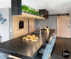 Landelijke keuken en schuifdeuren in white wash eiken kleur helemaal op maat gemaakt. Composiet aanrechtblad en stalen afzuigkap-schap.