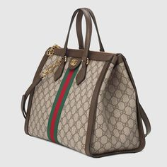 Shop the Ophidia GG medium top handle bag by Gucci. Imbued with retro-inspired references, the world of Ophidia evolves with the introduction of a medium top handle bag defined by a squared shape that recalls vintage designs. Crafted in GG Supreme canvas, the accessory features some of the most distinctive House codes, like the green and red Web stripe—a homage to the equestrian world—and the Double G from the '70s archives, here reworked with a sophisticated take. The bag is completed with…