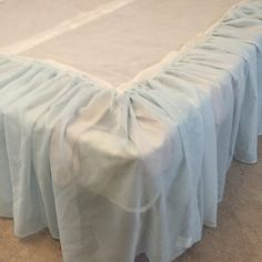 Learn how to take $2 curtains and make them into a tulle bed skirt or dust ruffle in under and hour!