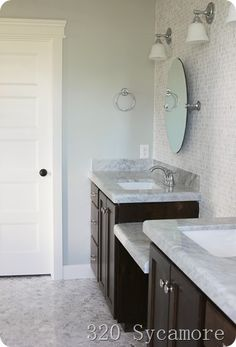 Sherwin Williams Silver Strand is one of the best gray paint colours with blue and green undertones. Shown in bathroom with marble and dark vanity