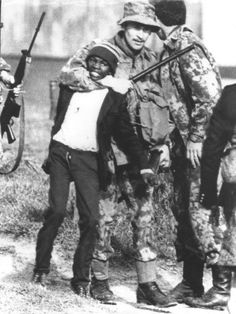 A South African policeman grabs a black student during rioting in Guguletu, near Cape Town, November 24, 1976.