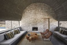 Materials such as unpolished stone, used for the interior walls speak louder than statement furniture or décor. Tagged: Living Room, Bench, Coffee Tables, Chair, Wood Burning Fireplace, Rug Floor, and Slate Floor.  Photo 5 of 10 in 4 Enchanting Moroccan Villas by French Duo Studio KO