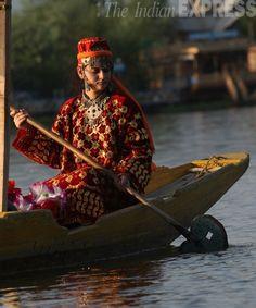 An Indian woman in traditional Kashmiri attire rows a boat across the Dal Lake in Srinagar, Kashmir. #India #Kashmir #photo