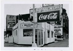 Exterior view of White Castle number 1. Located at 302 Virginia Ave. in Indianapolis, Indiana. Opened on July 9, 1927. Photograph was taken November 27, 1955. A large White Castle and Coca-Cola sign is pictured. White Castle sign reads 12 cent hamburgers. An advertisement on the building behind White Castle reads Royal Crown Cola.