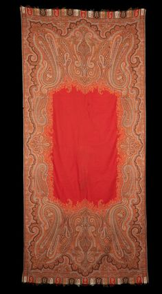 A woven Jamawar Shawl  Kashmir, circa 1875 of rectangular form, the red rectangular centre invaded by floral palmettes, the field woven with elongated boteh and curling kunjboteh in the corners, both ends with a register of arcades containing boteh and flowering plants  339 x 156 cm.
