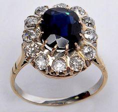 Anel de ouro amarelo 18k, com 13 diamantes de aprox. 0,05 ct e pedra azul. Aro 16. Peso: 4,3 g