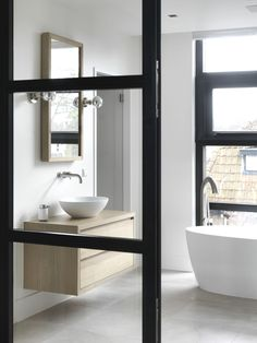 contemporary bathroom with free-standing tub and wall hung vanity