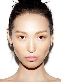 Contrasting orange eyeshadow lids and light pink pastel lips   allure.com