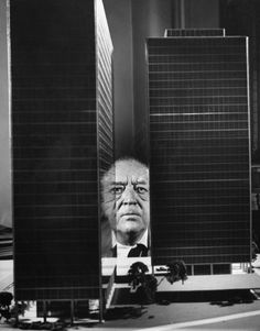 Architect Ludwig Mies van der Rohe peers between two large models of ultra-modern apartment buildings he designed for Chicago's Lake Shore Drive, 1956.