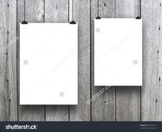 Close-up of two hanged asymmetrical blank frames with clips against monochrome wooden background