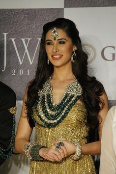 Nargis F show-casing stunning jewelry made of emerald stones, kundan, white…