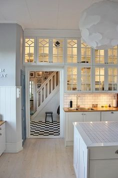White Kitchen With Glass-Fronted Cupboards. Loving how the light filled glass cupboards give the illusion that the room so much bigger.