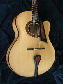 Otis Tomas makes guitars in my homeland of Cape Breton. This is a flattop with strong echoes of an archtop. Me likey.