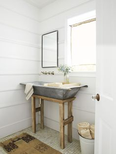 In this powder room, a simple wooden stand (and holes drilled for plumbing) transforms a Dutch galvanized metal hay-collecting bin into a statement-making sink.