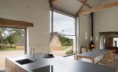 """The barn kitchen. Twenty years after Interior Design Hall of Famer John Pawson collaborated on acclaimed cookbook """"Living and Eating"""" with food writer Annie Bell, he decided to revisit the connection between food and architecture on a more personal level. #InteriorDesign #Homes #KitchenDesign John Pawson, Barn Kitchen, Farms Living, Fireplace Design, Architectural Digest, Beautiful Homes, Architecture Design, House Design, Campinas"""