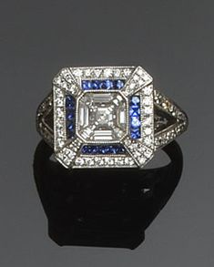 A diamond and sapphire square panel ring The central square cut-cornered brilliant bordered by trapezoid baguette-cut diamonds, within calibré sapphire detail, and outer border of small brilliants, between diamond set bifurcated shoulders, 18ct white gold mounted