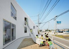 """MAD has draped the wooden structure of an old house in Japan in a """"skin"""" of white asphalt shingles to form a kindergarten with a curving roofline"""