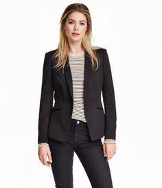 Een getailleerde blazer van jersey met smalle revers en schuine paspelzakken voort. Het model is gevoerd en heeft een split achter.