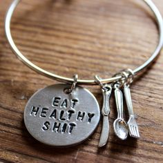 This bracelet is a perfect accessory for any foodie out there! One hand stamped charm, with a tiny silver spoon, fork and knife included to add some foodie flare. All charms are on a silver band that