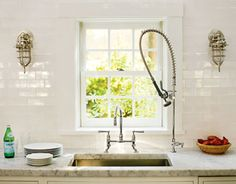 subway tile with white marble and a goose-neck bridge faucet