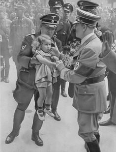 Adolf Hitler about to greet or hold a small child. The child looks rather hesitant!