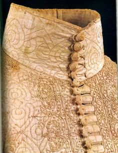 An embroidered linen doublet seen at close distance. Embroidery is simple, but very thick, real horror vacui at the work here. Linen doublets seem to be relatively common summer wear for the upper crust, but they felt that extensive decoration was needed to make it good enough for wearing. It's interesting to note that here there's no mix-up in materials, embroidery, buttons and ties are all linen.