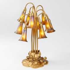 """""""Ten-Light Lily"""" Tiffany Table Lamp  A Tiffany Studios New York """"Ten-Light Lily"""" lamp, featuring ten golden Favrile glass shades suspended above a gilt bronze lily pad base"""