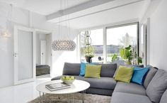 Stunning Living Room Idea with L Shaped Grey Fabric Cofa Living Room Design and Cute Blue Green Lime Pillows and Round Shaped White Coffee Table also Grey Fur Area and Drum Shaped Pendant Lamp