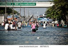 BANGKOK - NOVEMBER 13: A group of people evacuates from  the flooded area at Sapan Mai district during the massive flood crisis on November 13, 2011 in Bangkok.