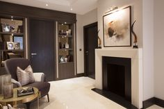 Luxury Lobby with bespoke bookcases and marble fireplace | JHR Interiors