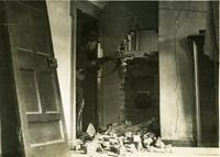 """Irish Free State Soldier in a badly damaged house - From UCD Digital Library, Desmond FitzGerald Photographs, Photograph by W.D. Hogan """"An Irish Free State Army soldier in firing position inside a badly damaged house. His rifle is pointed through a hole in the wall of a room; debris is lying on the ground and a door has been kicked off its hinges."""""""