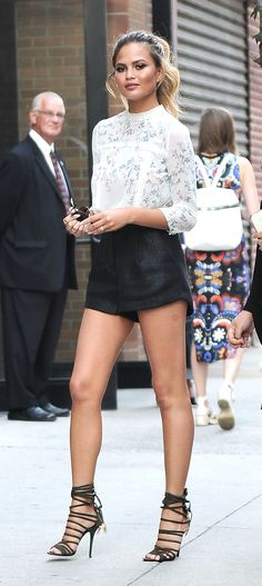 Chrissy Teigen wearing a high-neck prairie shirt, high-waist shorts, and sexy lace-up heels