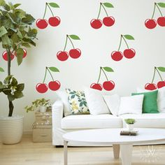 Large cherry wall decals on white wall behind a white couch making a cherry wallpaper pattern. Each cherry features a red base with a green leaf.