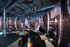 """Big Data Vortex"" - An immersive panorama of binary maps, gel electrophoresis tracks, overlapping sine waves and geodata mounted on a sweeping, arciform section of tubing. The graphic speaks to the ubiquity and increasing presence of Big Data in contemporary life. Photo by David Levene, courtesy of KRAM/WEISSHAAR"