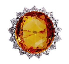 This spectacular 24.61ct yellow topaz takes you back to the glitz and glamour of the 1930s where all aspects of fashion were influenced by Hollywood. Made by the famous Italian jeweller, Filippo Chiappe the captivating oval double sided damier cut topaz is surrounded by old round cut diamonds.