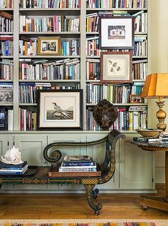 This living room library is brimming with cookbooks and decor books and antique furniture.