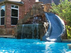 home outdoor pool with waterfall and stoned slide an oasis and also a playground in
