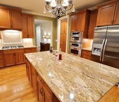 Gentil Oak Cabinets, Warm Light Granite Countertops, Stainless Appliances And  Green Walls.