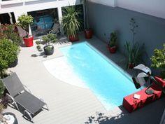 La citadine par l'esprit piscine - Piscine 2- 3,3 x 6,6 m Revêtement blanc Escalier sur mesure sur la longueur Margelles et plage en lames composite grises Trophée d'Or FPP 2011 de la piscine citadine de forme libre