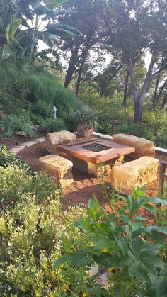 Sandstone seating blocks create a rustic and natural look to this fire table area set below the waterfall area.