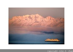 Sunrise highlights a Washington State Ferry as it crosses Puget Sound from Seattle to Bremerton, edging by a fog bank below a snowy Olympic Mountain Range. Olympic Mountains, Ferry Boat, When It Rains, Mountain Range, Far Away, Washington State, Pacific Northwest, North West, Airplane View
